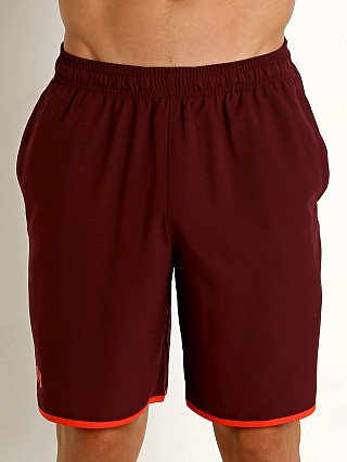 Model in dark maroon Under Armour Qualifier Woven Short
